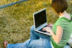 Casual Teen With Computer. Female Student working on laptop on bleachers royalty free stock photos