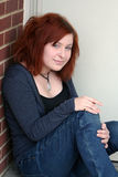 Casual Teen Sitting 5. Contemporary teen girl sitting in an outside doorway royalty free stock images