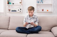 Casual teenage boy playing mobile game at home. Teenager playing online game on mobile phone and listening to music in earphones at home. Gadget addiction Stock Photos