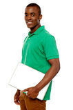Casual teenager carrying laptop Royalty Free Stock Images