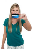 Casual teenager holding up credit card Royalty Free Stock Photo