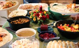 Casual Thanksgiving Feast on Table with Plates Being Filled. This is a Thanksgiving meal spread on table with centerpiece.  Around the edges are plates being Royalty Free Stock Image