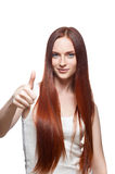 Casual thumbs up female. Vertical studio portrait of young attractive green-eyed caucasian female with long natural straight shiny red hair dressed in casual royalty free stock photography
