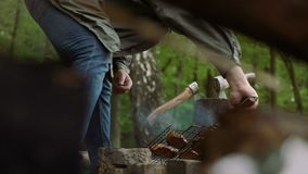 Casual tourist cooks delicious barbecue food on hot grill for outdoor friends party. stock footage