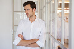 Casual upset businessman leaning against window Royalty Free Stock Photo