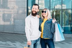 Casual urban shopping couple retail sale lifestyle. Casual urban shopping couple. Retail sale lifestyle. Smiling men and women with paper bags. Copy space for stock photo