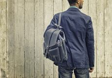 Man in blue suit and jeans with leather backpack. Casual wear detail: stylish man in blue suit and jeans with leather backpack on wooden background stock photo