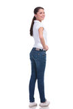 Casual woman back view. Full length picture of a casual young woman standing with her back to the camera and holding a hand on her hip while looking over the Stock Photo
