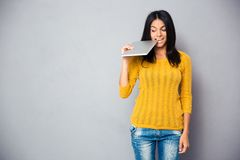 Casual woman biting tablet computer Stock Photography