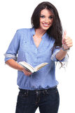 Casual woman with book shows thumb up Stock Photo