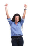 Casual woman cheering with both hands in air. Young casual woman cheering with both her hands raised in the air and smiling for the camera. on white background Stock Image