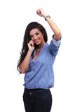 Casual woman cheering while on the phone Stock Photos