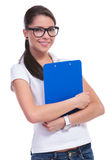 Casual woman with clipboard at chest Royalty Free Stock Image