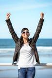 Casual woman on coast travel getaway. Coast travel joyful woman success. Happy successful hispanic girl enjoying trip to the beach raising arms and smiling on Stock Image