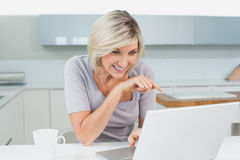 Casual woman with coffee using laptop in kitchen Stock Photography