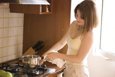 Casual woman cooking on stove