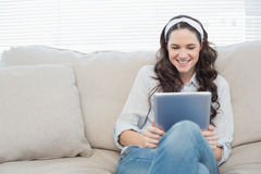 Casual woman on cosy couch using tablet pc Royalty Free Stock Images