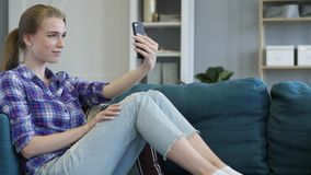 Casual Woman in Couch Taking Selfie on Smartphone stock image