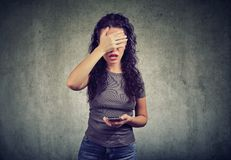 Woman covering face in despair having bad news on smartphone against gray background royalty free stock photo