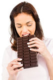 Casual woman crunching bar of chocolate Royalty Free Stock Image