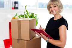Casual woman documenting list of goods on clipboard Stock Photos