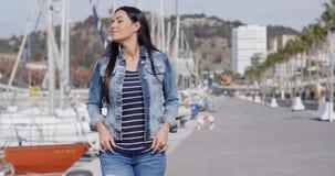 Casual woman enjoying a walk through a marina stock video footage
