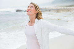 Casual woman with eyes closed stretching hands at beach Royalty Free Stock Photo