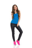 Casual Woman Front View. Young woman in blue shirt, black leather trousers and pink sneakers. Front view. Full length studio shot isolated on white Stock Images