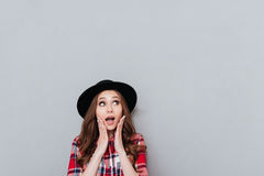 Casual woman in hat holding hands at her face. Portrait of a young shocked casual woman in hat holding hands at her face and looking away at copyspace isolated Royalty Free Stock Photo