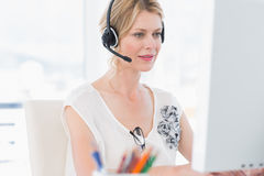 Casual woman with headset using computer Stock Images