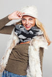 Casual woman holding her hat. On grey Royalty Free Stock Photos