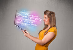Casual woman holding laptop with exploding data and numers. Attractive casual woman holding laptop with exploding data and numers royalty free stock photography