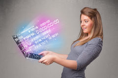 Casual woman holding laptop with exploding data and numers Stock Image