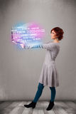 Casual woman holding laptop with exploding data and numers. Attractive casual woman holding laptop with exploding data and numers royalty free stock images