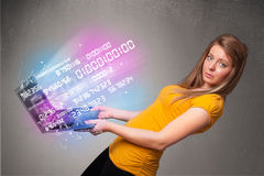 Casual woman holding laptop with exploding data and numers Stock Photos