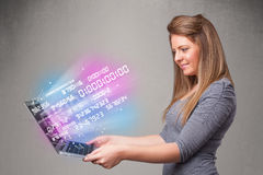 Casual woman holding laptop with exploding data and numers stock images