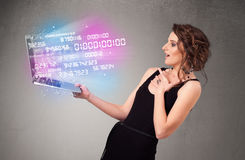 Casual woman holding laptop with exploding data and numers Stock Photo