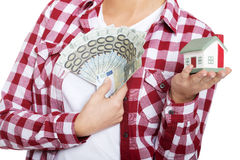 Casual woman holding money and house on hands. Royalty Free Stock Photos