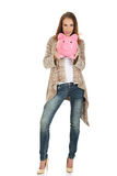 Casual woman holding piggy-bank. Royalty Free Stock Photography