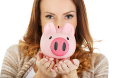 Casual woman holding piggy-bank. Royalty Free Stock Image