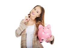 Casual woman holding piggy-bank. Royalty Free Stock Images