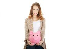 Casual woman holding piggy-bank. Royalty Free Stock Photos
