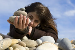Casual woman holding stones in the beach Royalty Free Stock Image
