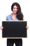 Casual woman holds a blackboard with both hands Stock Image