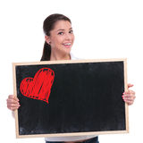 Casual woman holds blackboard with heart Royalty Free Stock Photo