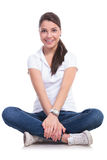 Casual woman holds crossed  legs Stock Photos
