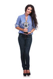 Casual woman holds her trophy and smiles Royalty Free Stock Image