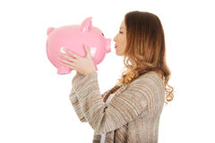 Casual woman kissing piggy-bank. Stock Photo