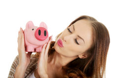 Casual woman kissing piggy-bank. Stock Photos