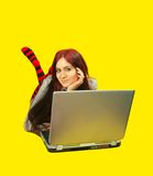 Casual woman with laptop. Pretty  girl with personal computer over yellow Stock Photography